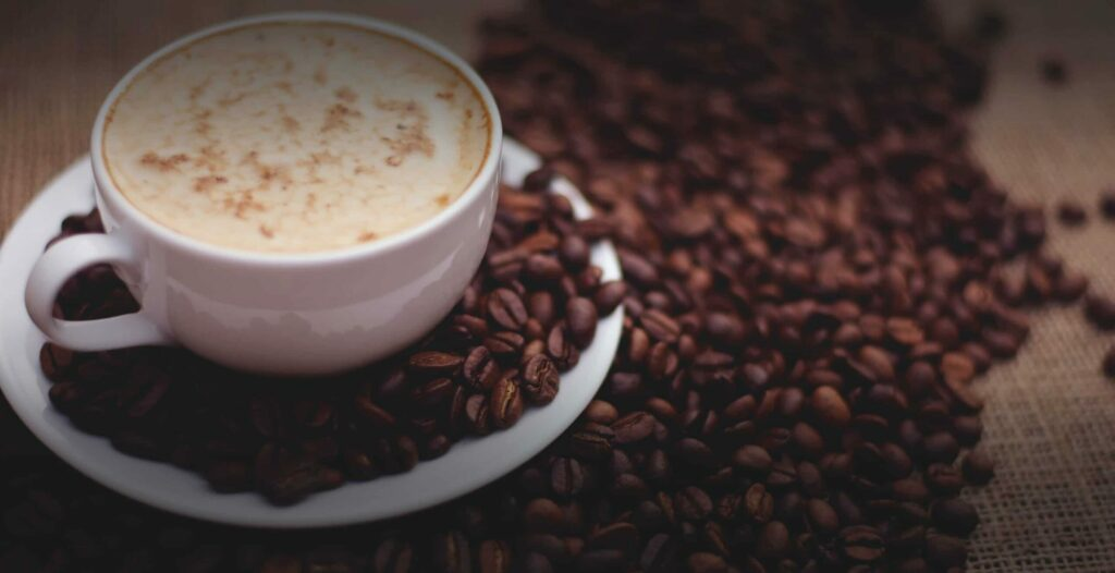 Capuccino servi avec grains de café sur une table