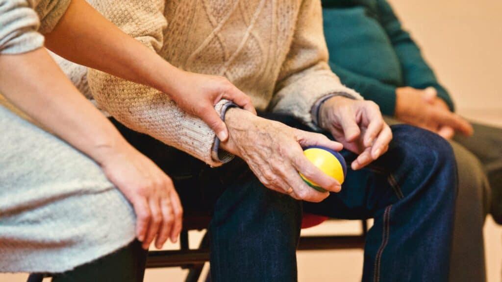 aide soignante attrapant la main d'une personne agée