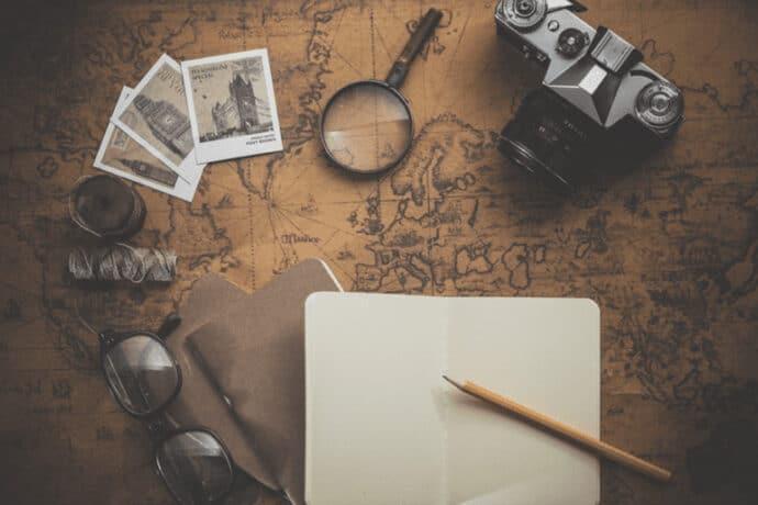 bloc notes posé sur une carte du monde avec boussole et appareil photo pour voyager
