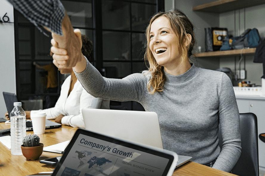 jeune femme souriante saluant un collègue dans une salle de réunion
