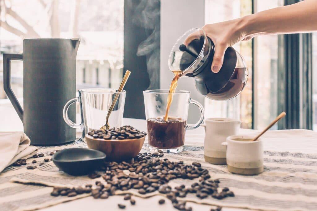 main versant du café en grain dans une tasser en verre avec des grains de café sur la table