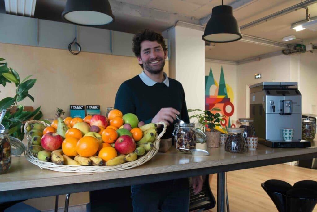 un homme devant une corbeille de fruits des snacks et du cafe braam