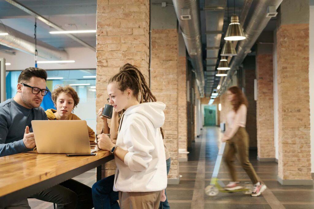 equipe qui travaille sur une table haute autour d un ordinateur
