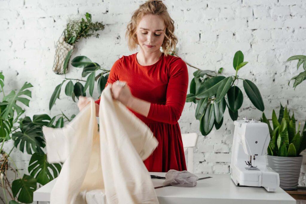 femme qui est en train coudre un petit chandail avec des plantes derrières
