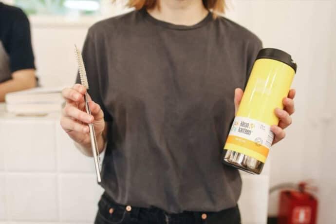 femme avec t-shirt gris tenant dans sa main une gourde d'eau.
