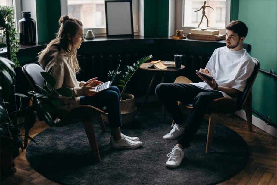 une femme et un homme sont dans un canapé en train de travailler sur un projet important