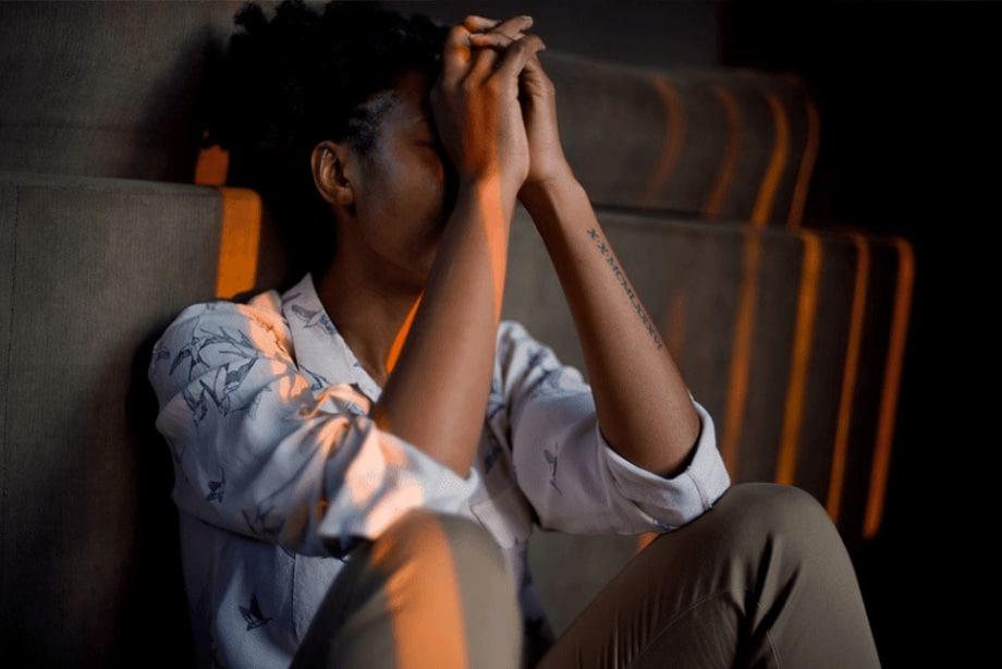 jeune femme pensive, assise par terre, genoux pliés et mains sur le visage.