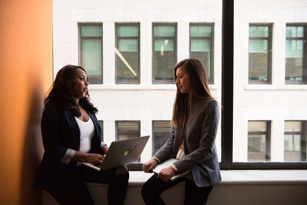 Deux femmes qui discutent au travail devant une fenêtre avec un ordinateur portable