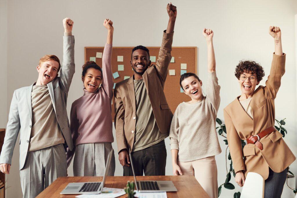 un groupe de collègue a un air triomphant en réunion