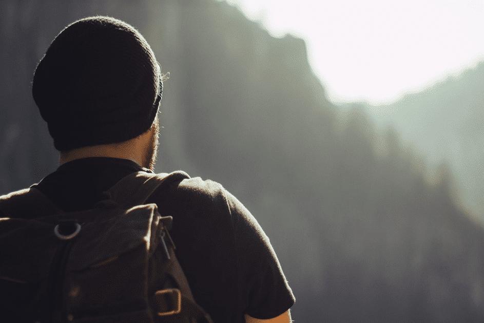jeune homme de dos avec sac à dos et bonnet devant une montage de sapins