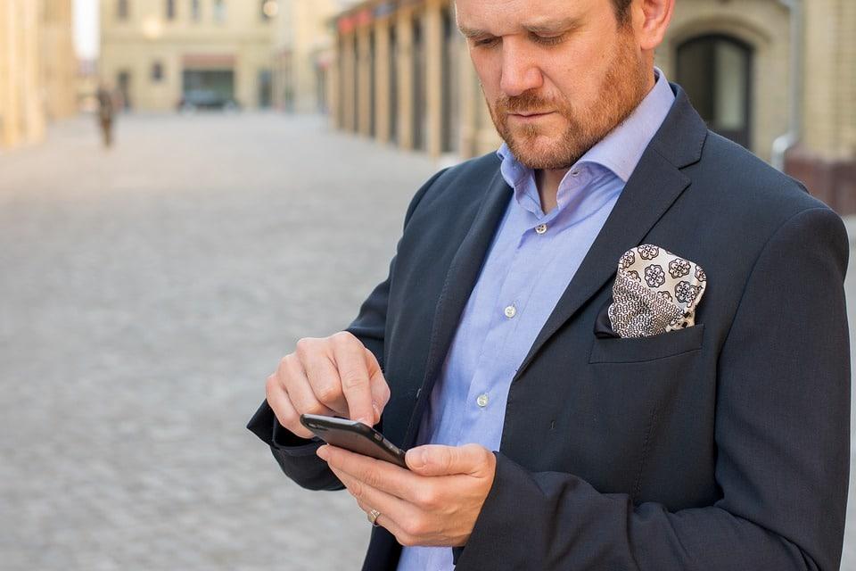 un homme écrit sur son téléphone