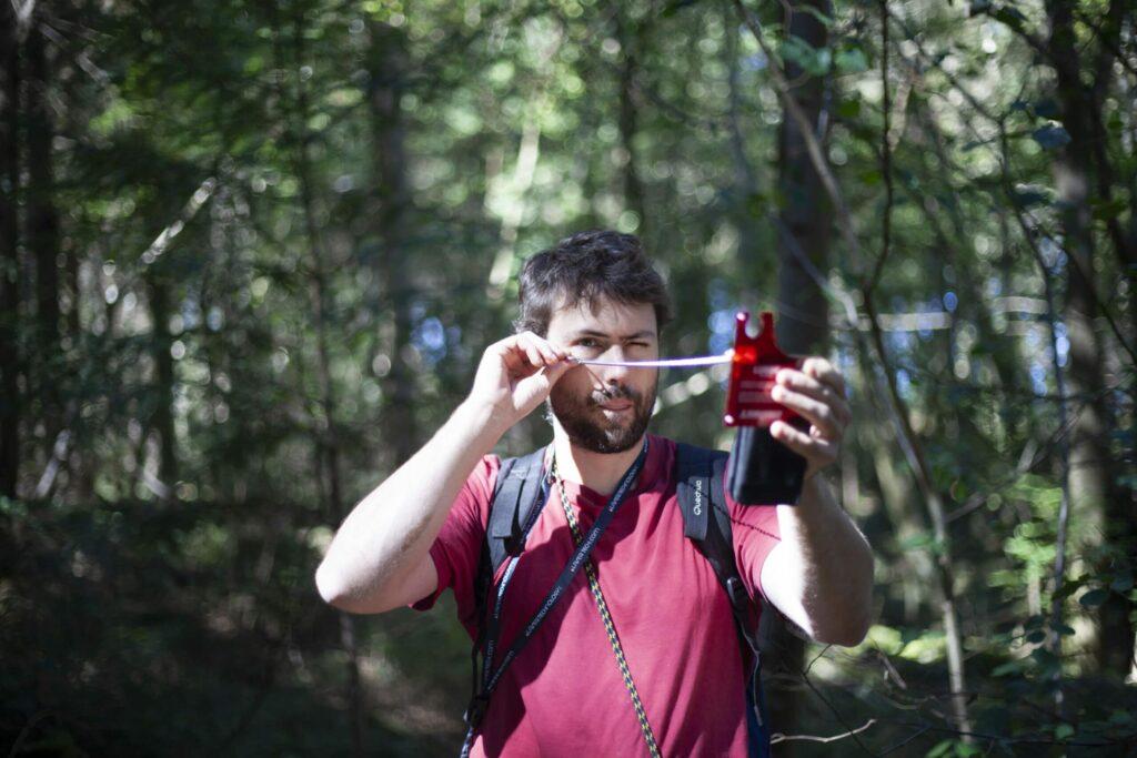 homme portant un t-shirt bordeau prenant des mesures dans une forêt.