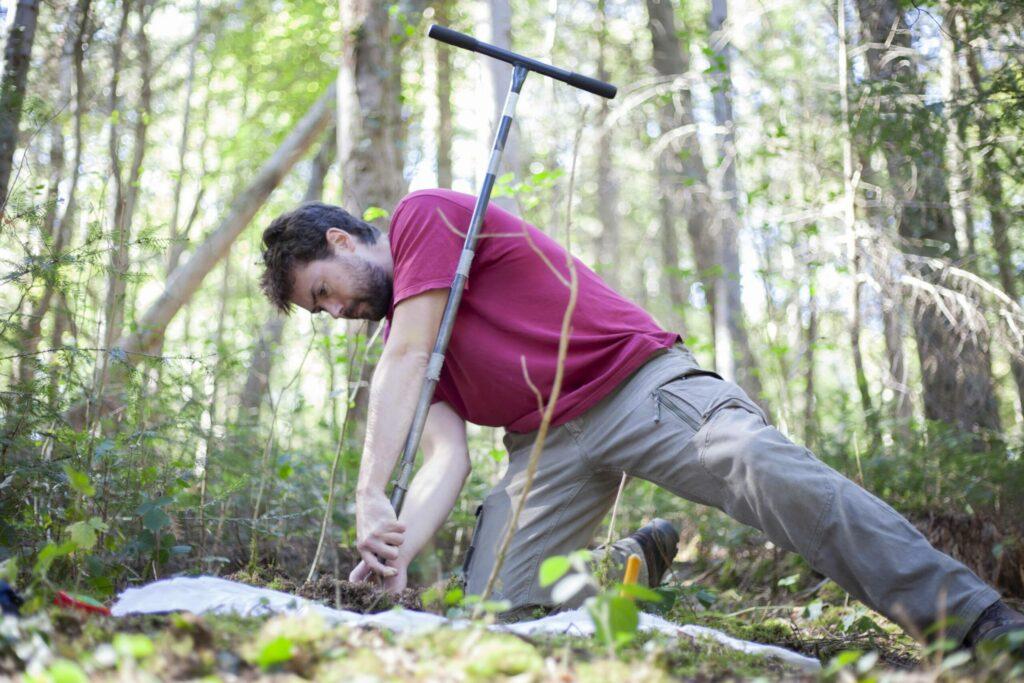 homme au t-shirt bordeau creusant un trou dans la terre en plein forêt.