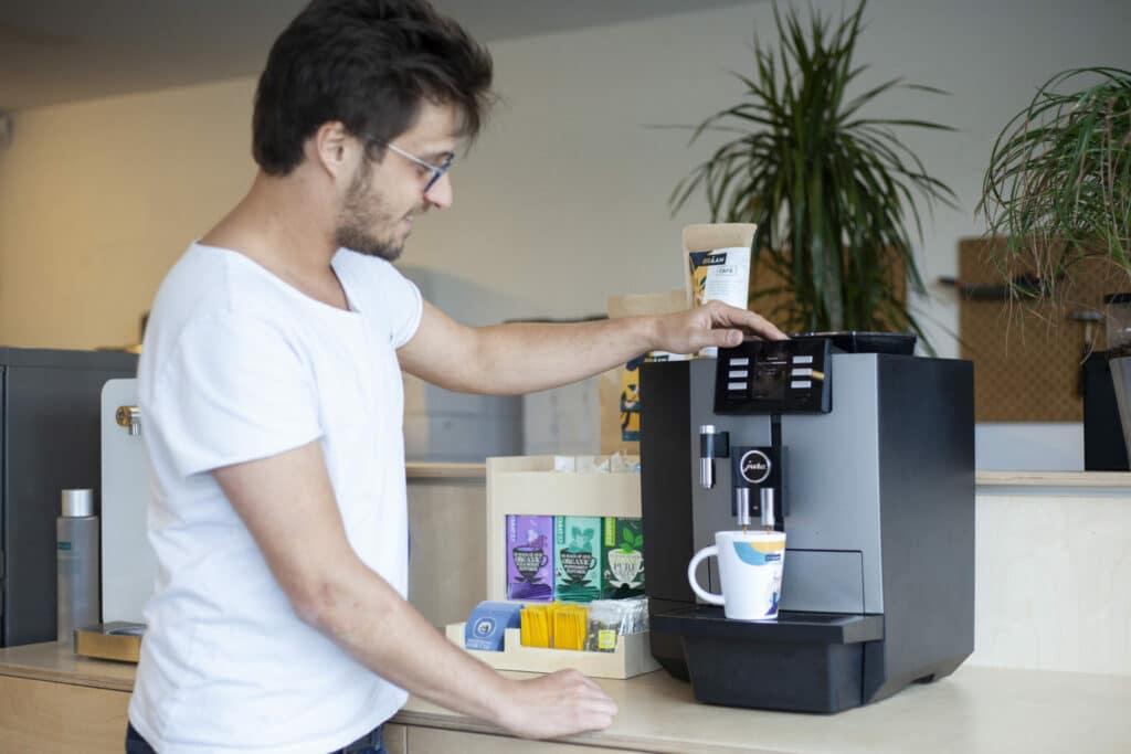 Un homme se fait couler un café dans une machine a cafe en grains