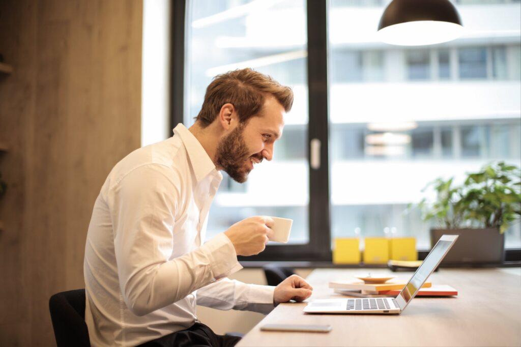 jeune homme souriant buvant une tasse de café en grains brâam devant son ordinateur portable