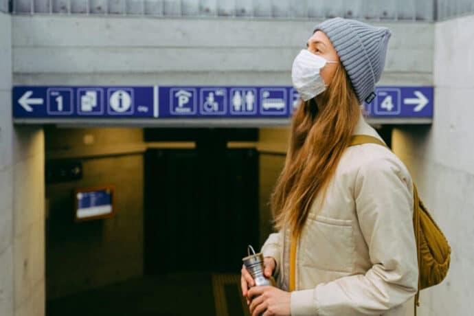 jeune femme portant un bonnet et un masque pour se protéger du covid devant une bouche de métro