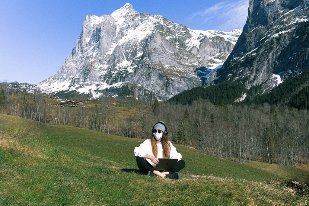 une jeune femme masquée écoute de la musique en pleine nature avec la montagne derrière elle