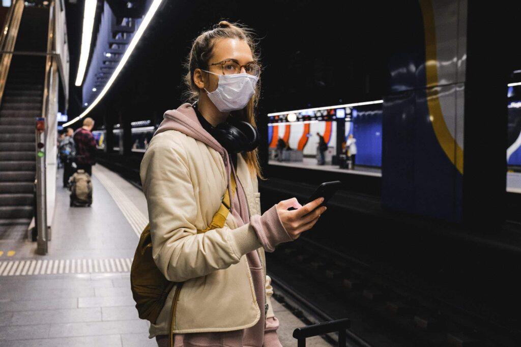 une jeune femme attend le métro sur le quai, masquée, en écoutant la musique, téléphone portable à la main