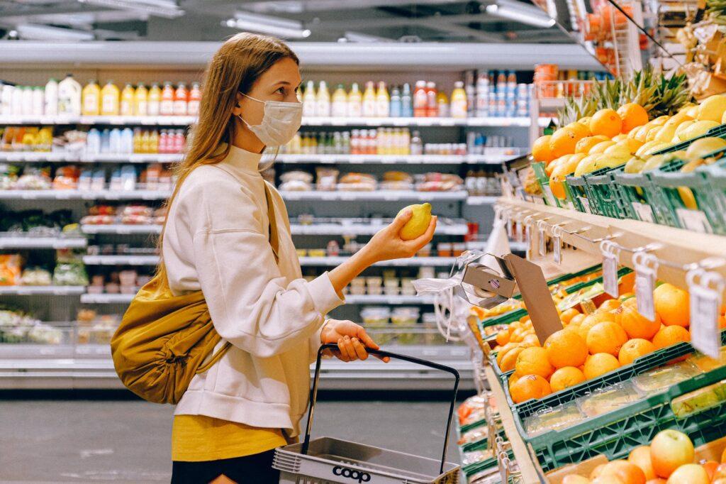 jeune masque masquée choisit des oranges dans le rayon fruits et légumes d'un supermarché, un panier à la main