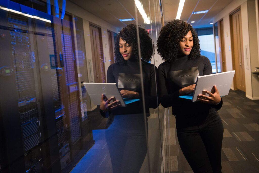 jeune femme dans un couloir de son entreprise portant un pc portable