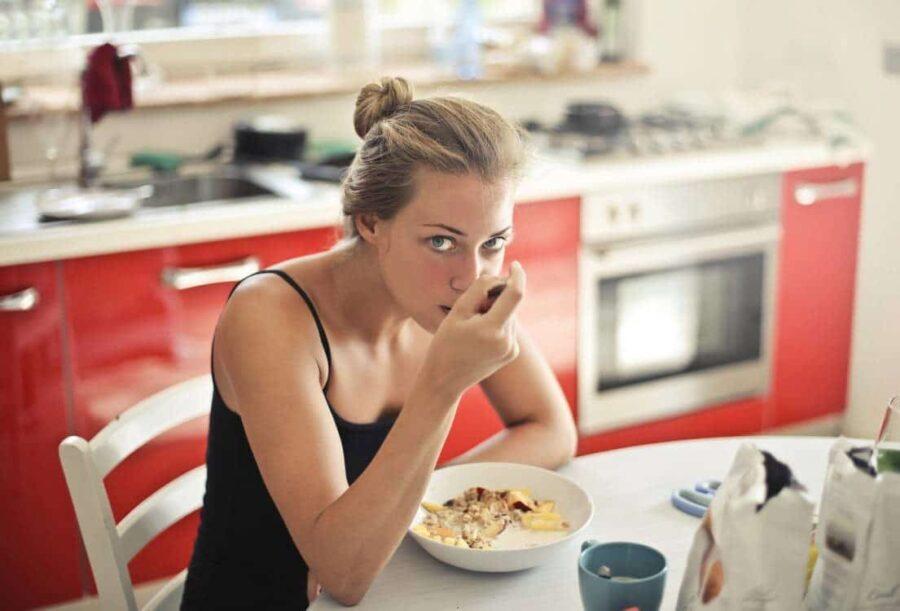 jeune femme mange son petit dejeuner muesli lait belle cuisine