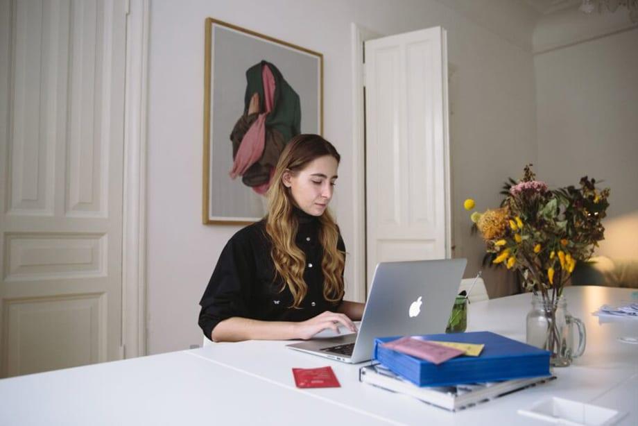 jeune femme qui travail au bureau sur son ordinateur avec une plante