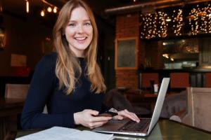 jeune femme souriante devant son ordinateur portable qui travaille