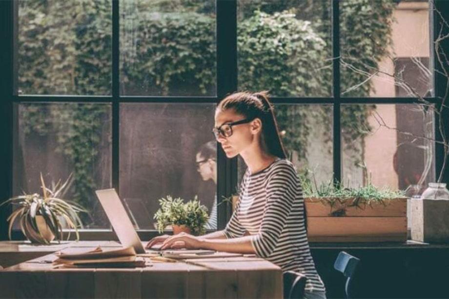 jeune femme travaillant devant son pc portable dans un endroit chaleureux et agréable