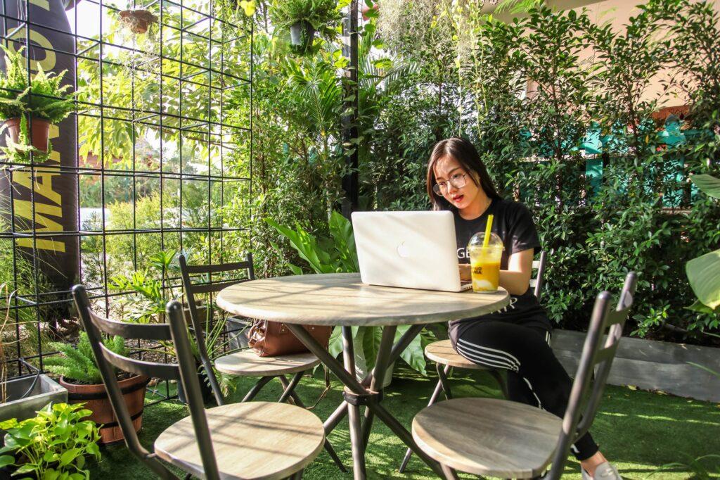 jeune femme travaillant avant son pc portable en extérieur arboré avec un jus de fruits frais