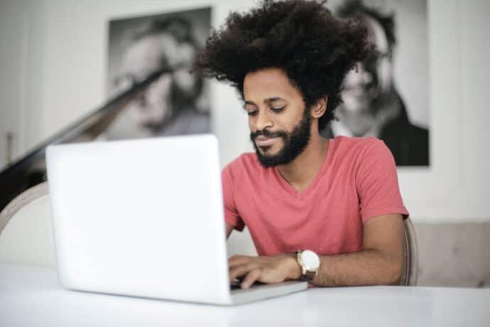 jeune homme qui travaille sur un ordinateur portable et qui est heureux
