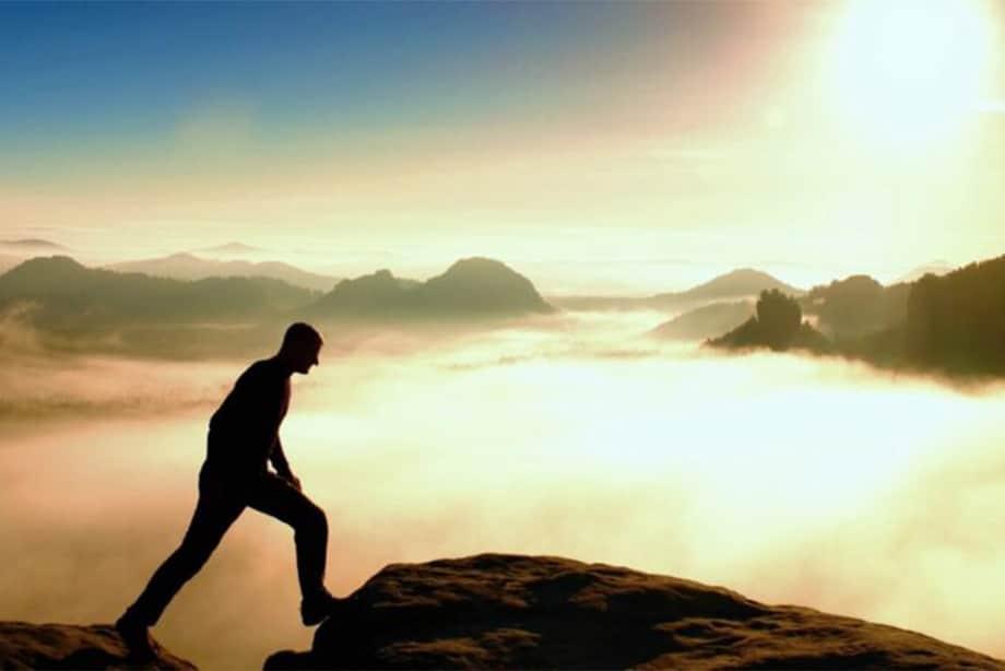 un sportif est au sommet d'une montagne au levé de soleil