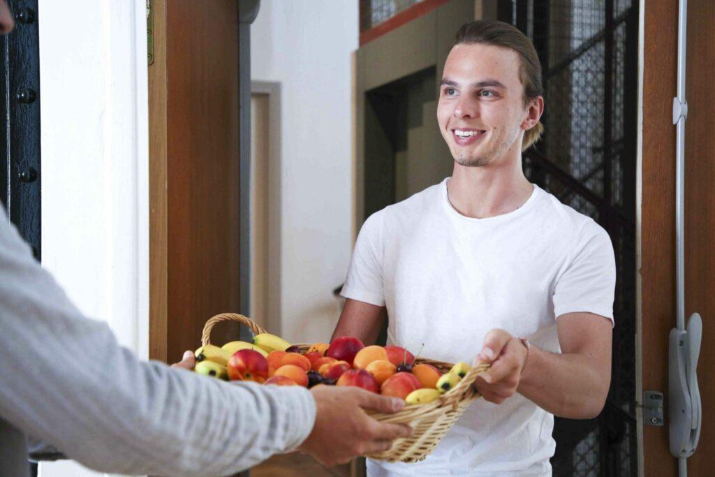 jeune homme qui livre une corbeille de fruits bio sans déchet