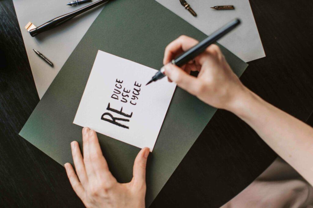 personne qui tient un feutre et qui écrit sur une feuille de papier des mots relatifs à l'écologie