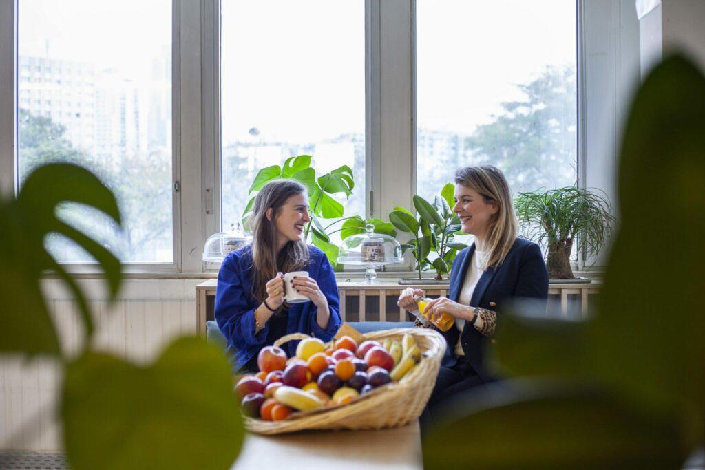 deux jeunes femmes prennent une pause conviviale devant une corbeille de fruit Brâam
