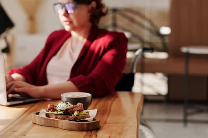 une femme travail à son bureau en mangeant une tartine