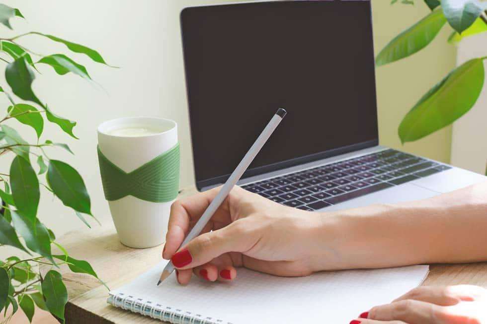 jeune femme qui écrit sur un bloc note devant son pc portable
