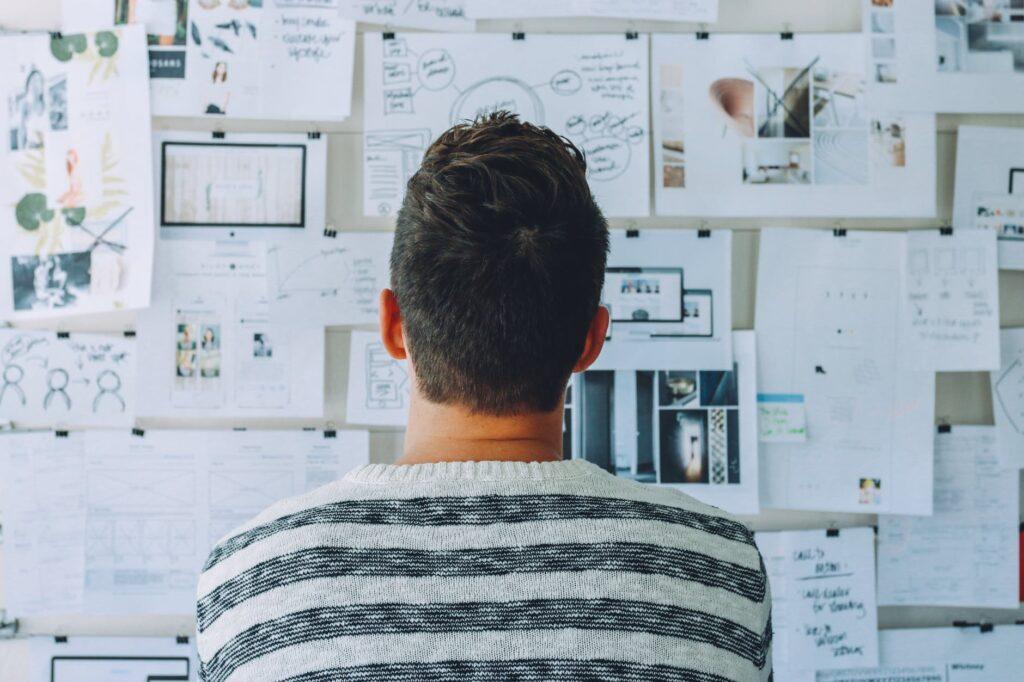 un jeune homme est en réflexion devant une mindmap