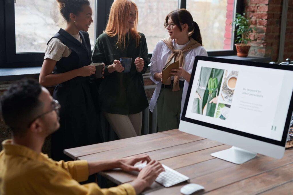 jeunes travailleurs discutant autour d'une jeune homme travaillant sur son ordinateur portable