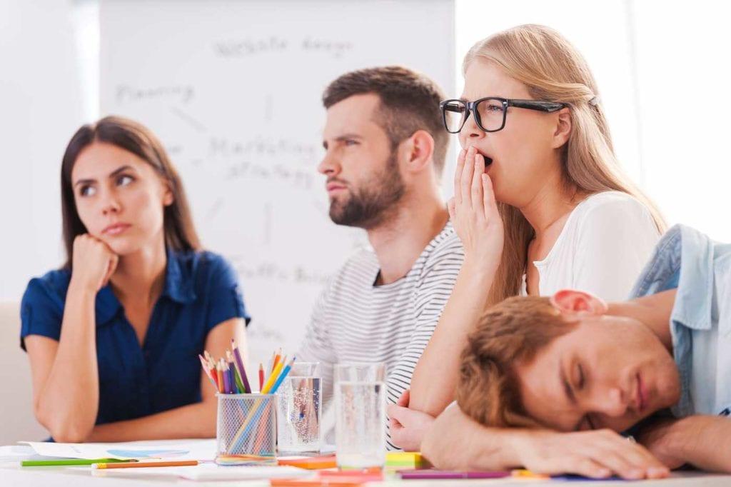 réunion de travail ennuyeuse avec une femme qui baille et un homme qui dort