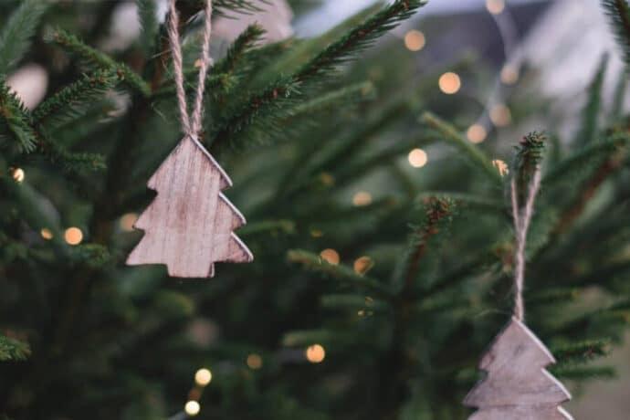 décorations en forme de sapin en bois accrochées à un sapin de noël