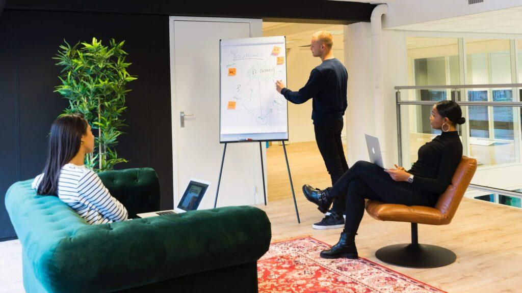 jeune homme devant un tableau lors d'une réunion de travail devant 2 jeunes femmes. avec un ordinateur.