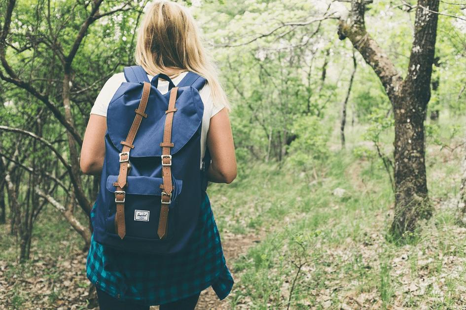 jeune femme en randonnée avec un sac à dos bleu dans la forêt